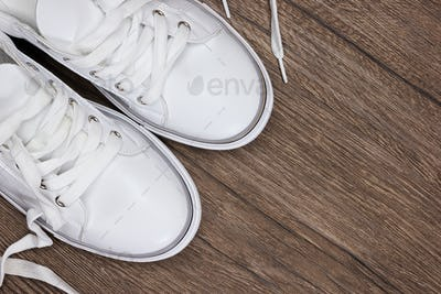 White sneakers on dark wooden surface