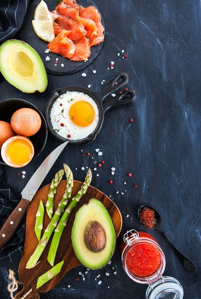 Top view of breakfast table with fried eggs, avocado, asparagus,