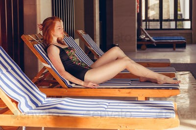 Portrait of pretty cheerful woman relaxing at the luxury poolside