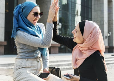 Islamic friends high five and smiling