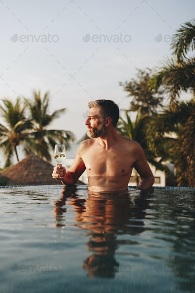 Man drinking wine in a swimming pool