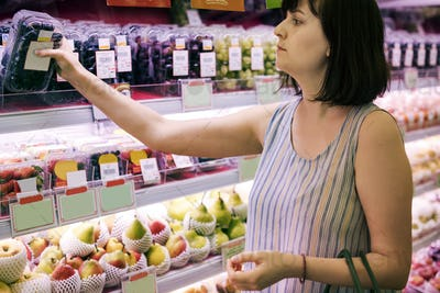 Woman selecting some grapes at the supermarket