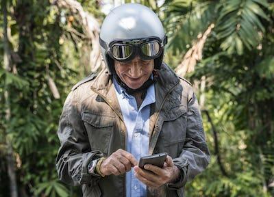 Mature biker checking his phone