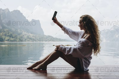 Woman using her phone by a lake