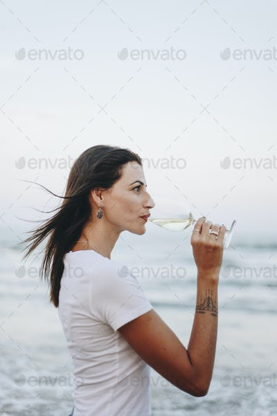 Woman drinking a glass of wine by the beach