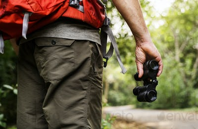 Man holding binoculars in the forest