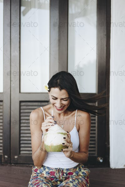 Woman drinking a fresh coconut