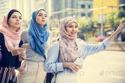 Islamic friends calling taxi on the street