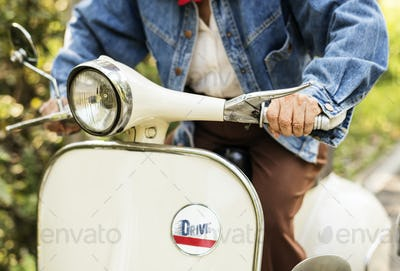 Closeup of a woman riding a classic scooter