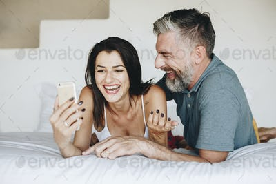 Couple using a smartphone in bed