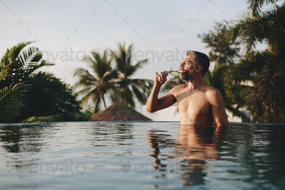 Handsome man having a glass of wine in the pool