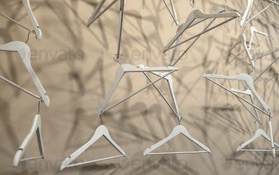 Empty wooden clothes hangers casting deep shadows