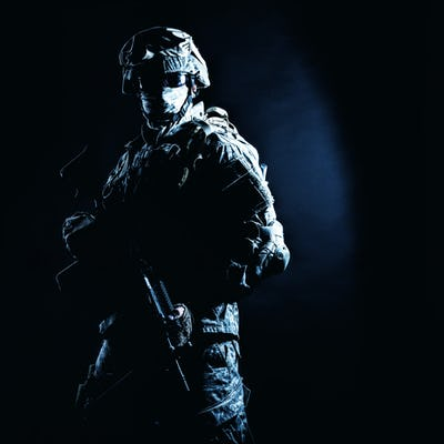 Infantry rifleman standing with weapon in darkness