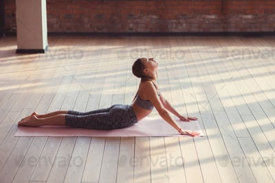 Young instructor doing yoga indoors