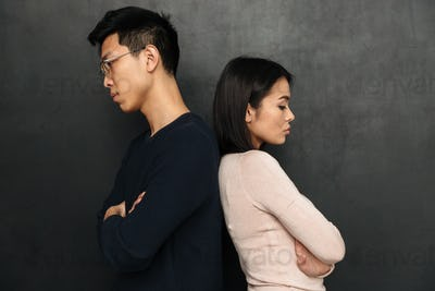 Side view of Offended couple standing back to each other