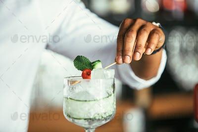 Bartender hands decorating cocktail