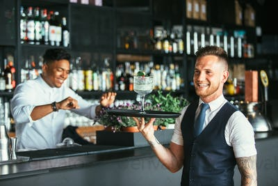 Smiling waiter with a cocktail
