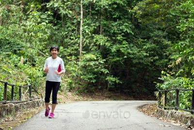 Front view of senior woman jogging through park