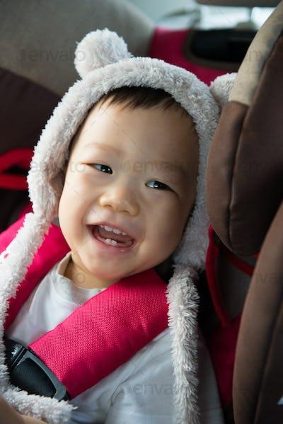Portrait of cute toddler boy sitting in car seat.