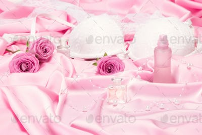 Perfumes with roses and women underwear on pink silk