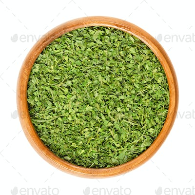 Dried parsley in wooden bowl over white