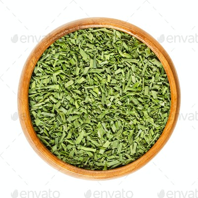 Dried chives in wooden bowl over white