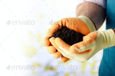 Farmer shows soil in his hands weared in gloves