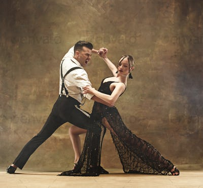 Flexible young modern dance couple posing in studio.