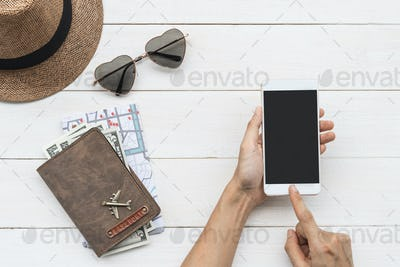 Traveler holding smart phone with passport and map, Travel concept