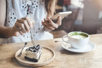 Young woman using smart phone and eating cake