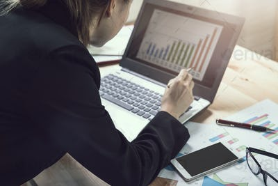 Businesswoman working on Desk office with marketing graph statistics analysis