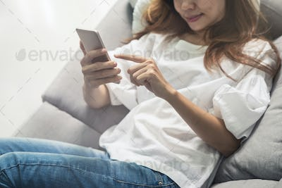 Young woman using smartphone at cozy home on sofa in living room