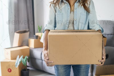 Young happy woman moving in new home and carrying cardboard boxes
