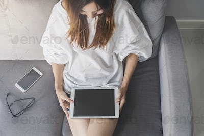 Young asian woman using tablet at home