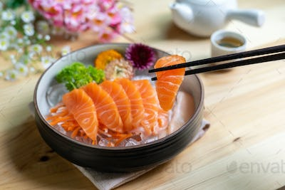 Salmon sashimi slice fresh serve on ice with tea, Japanese style