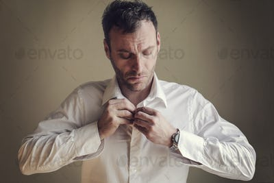 Man fastening his shirt