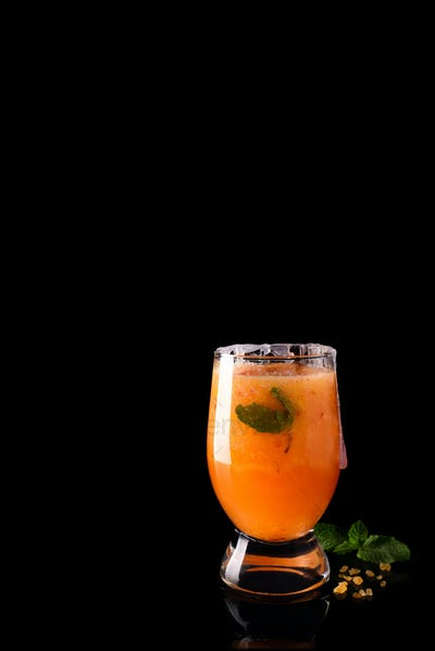 Paloma cocktail with fresh grapefruit, orange and mint on a black glass background