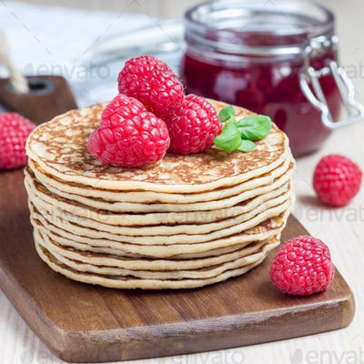 Stack of pancakes or fritters with raspberry on wooden board, ra
