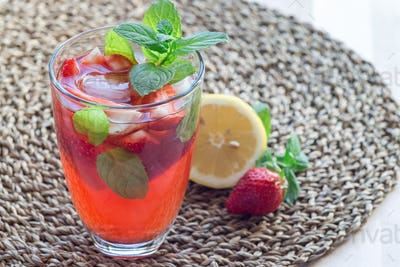 Glass of refreshing iced tea with strawberries and mint, horizon