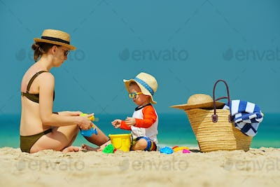 Toddler boy playing with mother on beach
