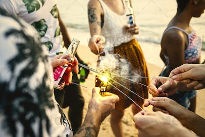 A diverse group of friends enjoying sparklers at the beach toget