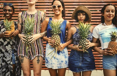 A diverse group of women standing and holding pineapple together