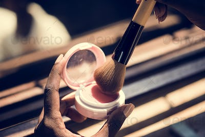 Closeup of woman using blush on