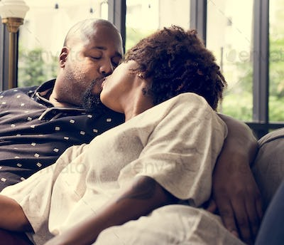 Black couple kissing on the couch