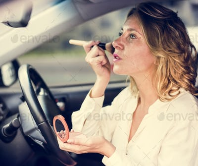 Woman wearing makeup in a car