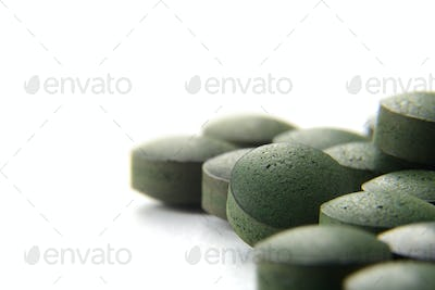 Pure Organic Spirulina Tablets Over white Background