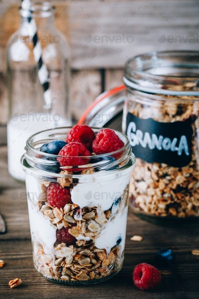 Healthy blueberry and raspberry parfait with greek yogurt in glass mason jar on wood background