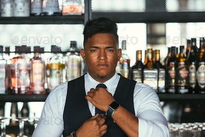 Elegant expert bartender put on the tie