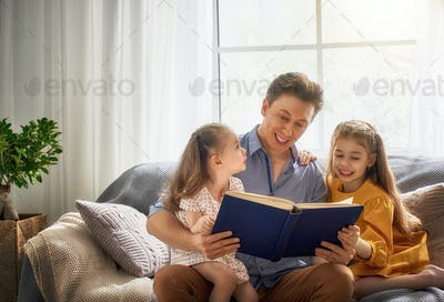father reading a book to his daughters