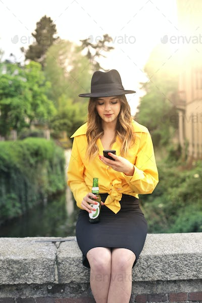 Girl with a beer and a smartphone